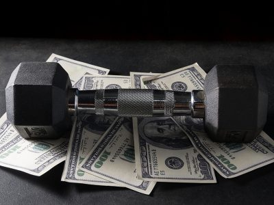 A dumbbell sitting on top of money