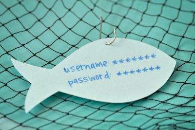 Username and password written on a paper note in the shape of a fish attached to a hook - Phishing and internet security concept