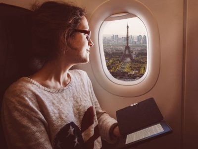 Woman looks out of an airplane window at the Eiffel Tower