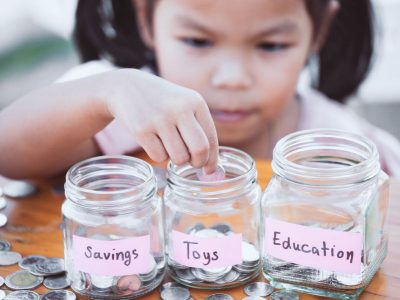 Little girl saving money in jars