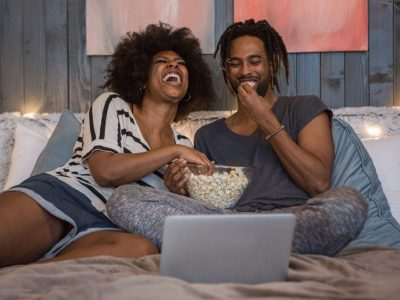 Couple eats popcorn while watching tv