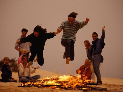 Two people jumping over a bonfire