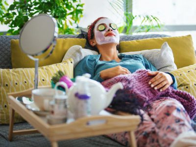 Woman lounges on a couch wearing a face mask for an at-home spa day
