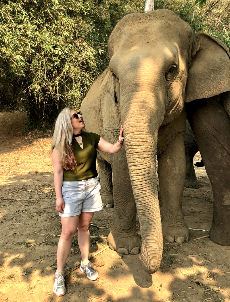 Emily stands next to an elephant