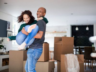 Man carrying woman in a new house surrounded by boxes