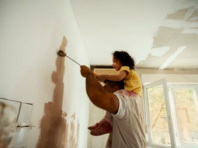 Daughter sits on father's shoulder as he paints the wall with a roller