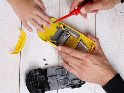 Hands fix a yellow toy car