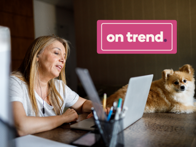 """On trend"" banner over woman working at home on her laptop next to her dog"