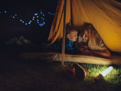 "Mother and child ""pretend camping"" in a makeshift tent on a mattress with a string of lights in the background."