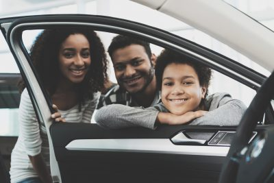 Image shows an family with a woman, man and young boy peering through the window of a new car.