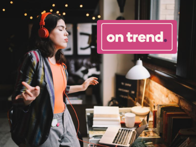 """On Trend"" box over image of a woman in headphones dancing in front of her laptop"
