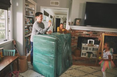 Man and woman leaning on a big piece of furniture that's wrapped in packaging tape, the guy is also about to toss a toy ball to a young girl