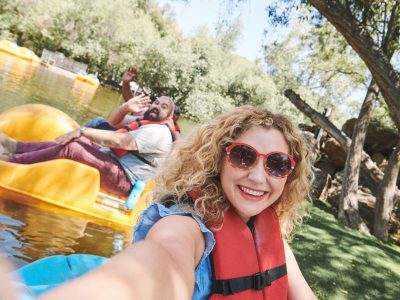 Woman takes a selfie while paddle boating with friends