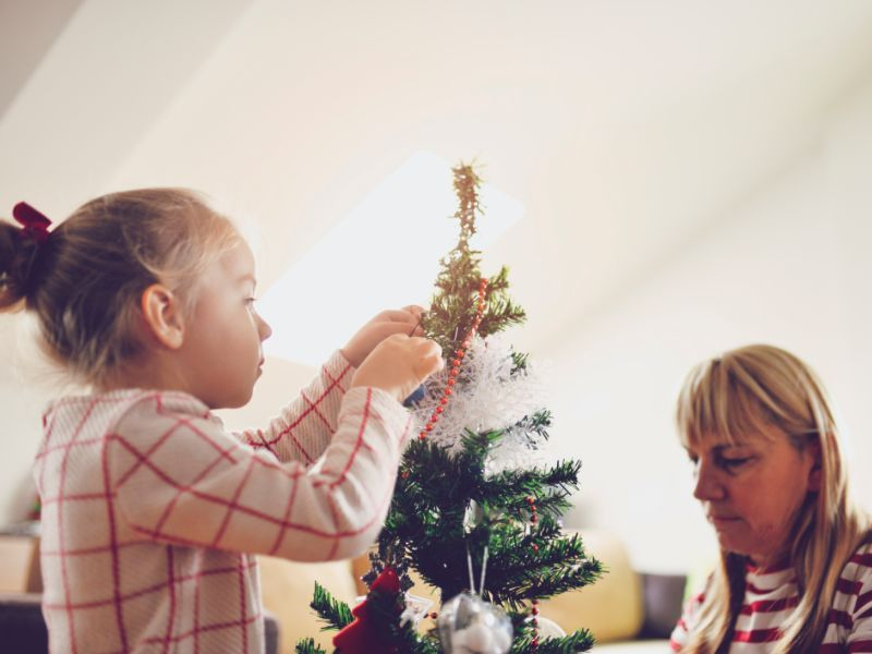 Little girl and grandmother decorate a tree with ornaments