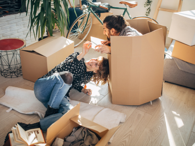 Man and woman having fun with cardboard boxes while packing