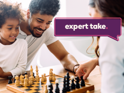 "Image shows a family playing chess together. Tag reads ""Expert Take""."