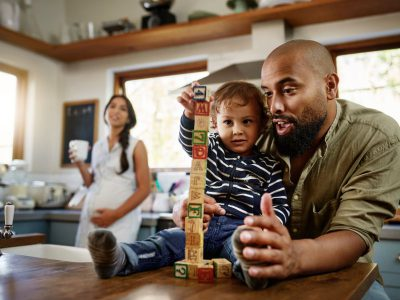 Image shows a father stacking blocks with his young son, while his pregnant wife watches them from the background.